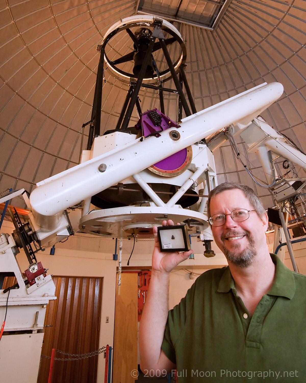 Richard Kowalski com um pedaço do meteorito Almahata Sitta, em frente ao telescópio que descobriu o asteroide 2008 TC3, que deu origem ao meteorito. Fonte: planetary.org