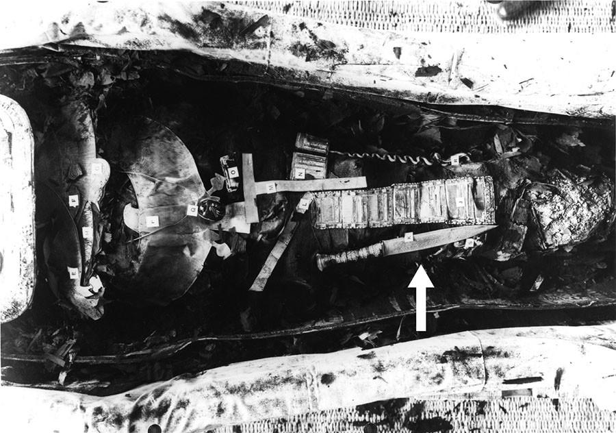 Imagem da múmia de Tutancâmon mostrando a adaga de ferro (34,2 cm de comprimento) colocada na perna direita (seta indicativa) (Comelli et al., 2016).